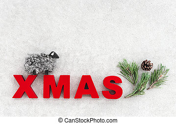 Simple Christmas decor in Nordic style. Little sheep, pine tree branch, cone and the word Xmas on concrete background.