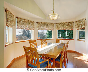 Simple dinning room with hardwood floor and chairs.