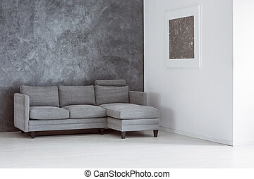 Simple empty living room with grey sofa against concrete...