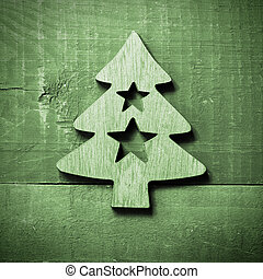Simple green Christmas tree with stars on green wooden background.