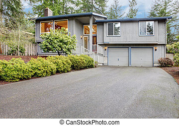 Simple grey brown split level with two garage doors.