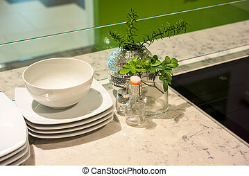Simple home table setting with flowers, glasses and cutlery in the kitchen interior.