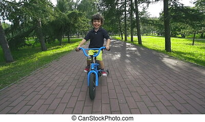 Simple Joy - Little boy approaching camera cycling in park...