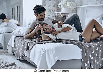 Simple joy of loving. Attractive young people lying on the...