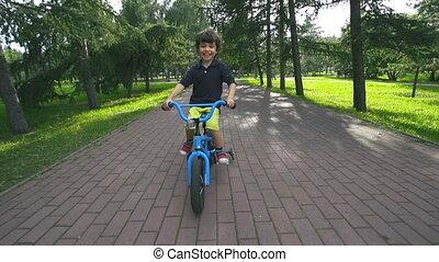 Simple Joy - Little boy approaching camera cycling in park...