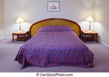 Simple light comfortable bedroom in hotel; big bed and two bedside tables with lamps