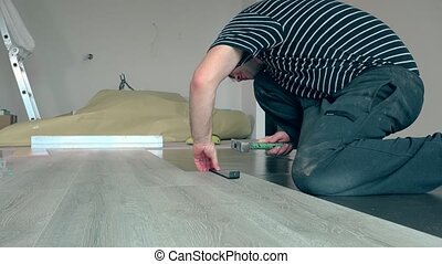 Simple man laying laminate boards on floor with hammer.