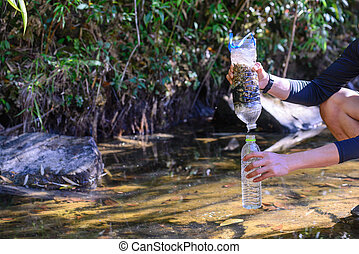 Simple natural water filtering gear use for outdoor camping.