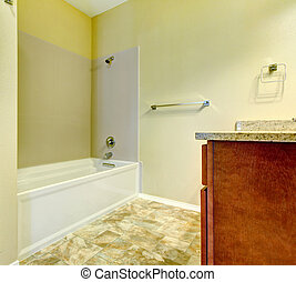 Simple new bathroom interior with white tub and wood cabinet.