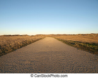 A simple empty gravel road through beautiful ranch grass lands