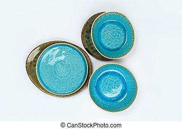 Simple rustic handmade blue crockery on a white background
