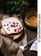 Simple rustic homemade food: a sandwich with ham and mustard on an old wooden table
