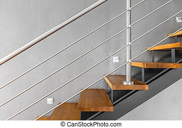 Villa interior with staircase with chromed railing and decorative grey wall finish