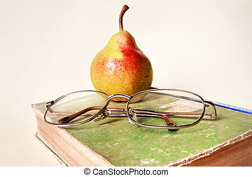 simple still life of pear, very old book and old glasses