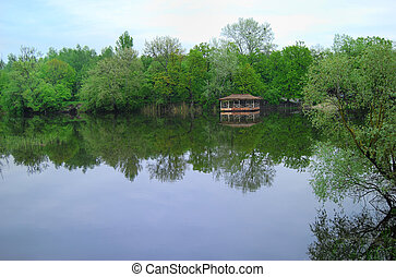 Simple wooden arbour on the bank of lake