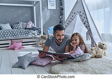 Simply being around. Father reading a book to his daughter...