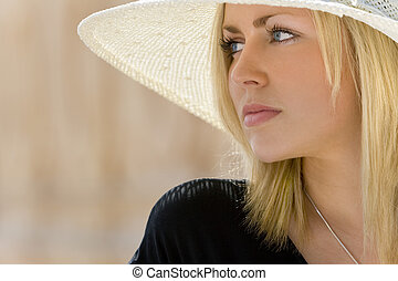 Portrait of a stunningly beautiful young blond woman wearing a classic wide brimmed hat