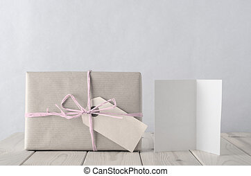 Photograph of a gift box wrapped in brown paper, tied to a bow with with pale icy pink raffia and with blank parcel tag label facing front. Beside it is a blank open greeting card on an old planked wooden table. Processed to create retro or vintage style in pale pastel hues.