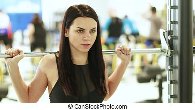 Simulator with a barbell - Beautiful girl doing exercises on...