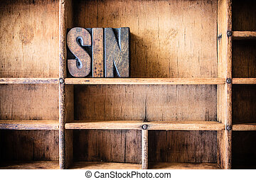 The word SIN written in vintage wooden letterpress type in a wooden type drawer.
