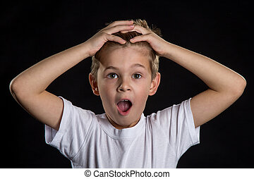Sincere emotions of people. Shocked and surprised boy with open eyes and mouth on the black background.