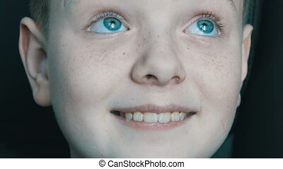 Sincere good cheerful baby face of blue-eyed blond boy with...