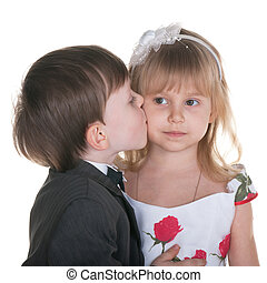 Sincere kiss - A little boy in suit kisses a little girl in...