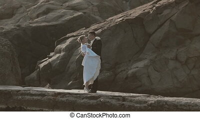 Sincere newlyweds dancing on the seaside near cliffs -...