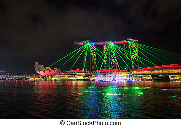 Singapore city at night with laser show in marina bay water front