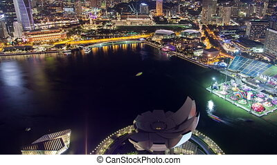 Singapore cityscape with yachts on water night time-lapse. pan up