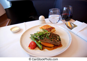 SINGAPORE - JULY 22, 2016: Business Class meal in a plane with red wine