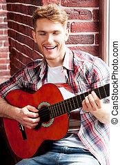 singende, seine, liebling, song., hübsch, junger mann, spielende gitarre, und, singende, während, sitzen, auf, der, fensterbank
