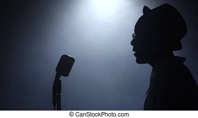 Singer approaching the microphone in smoke and white light sings. Black background. Silhouette. Slow motion. Close up