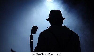 Singer at the microphone in smoke and white light sings. Black background. Silhouette. Slow motion. Close up