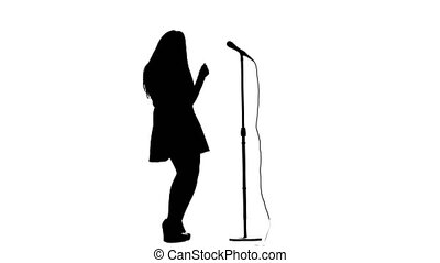 Singer dances to the beat of her song. White background. Silhouette. Side view