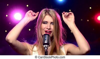 Singer female with retro microphone, hands up and looks into the camera, strobe lighting effect, close up, slow motion