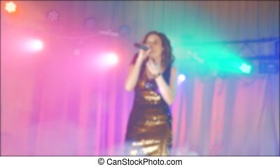 singer girl brunette sings blurred background night beautiful light with microphone. slow motion video. Singer in silhouette. Frontman woman silhouette singing to the microphone to the crowd on a concert lifestyle in a stage backlights
