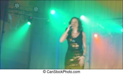 singer girl brunette sings blurred background night beautiful light with microphone. slow motion video. Singer in silhouette. Frontman woman silhouette singing to the microphone to the crowd on lifestyle a concert in a stage backlights
