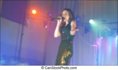 singer girl brunette sings blurred concert night beautiful light with microphone. slow motion video. Singer in silhouette. Frontman woman silhouette singing to the microphone to the crowd on a concert lifestyle in a stage backlights