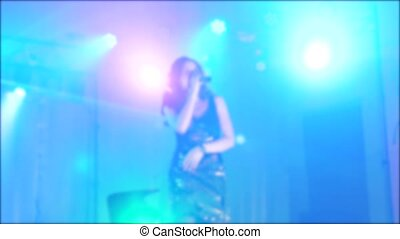 singer girl brunette sings blurred concert night beautiful light with microphone. slow motion video. Singer in silhouette. Frontman woman silhouette singing to the microphone to the crowd lifestyle on a concert in a stage backlights