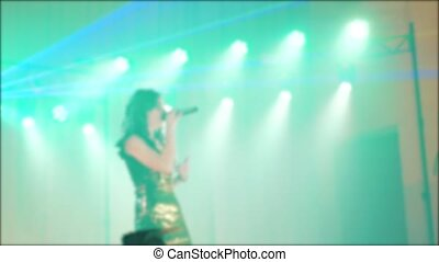 singer girl brunette sings blurred concert night beautiful light with microphone. slow motion video. Singer in silhouette. Frontman woman silhouette singing to the microphone lifestyle to the crowd on a concert in a stage backlights