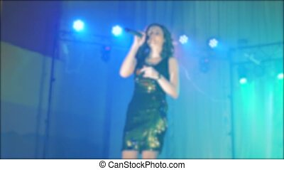 singer girl brunette sings blurred concert night beautiful light with microphone. slow motion video. Singer in silhouette. Frontman woman silhouette singing to the microphone to the crowd on a concert in a lifestyle stage backlights