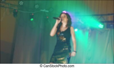 singer girl brunette sings blurred concert night beautiful light with microphone. slow motion video. Singer in silhouette. Frontman woman silhouette singing to the microphone to the crowd on a concert in a stage backlights lifestyle
