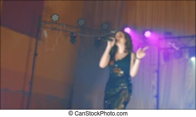 singer girl brunette sings blurred concert night beautiful light with microphone. slow motion video. Singer in silhouette. Frontman woman silhouette singing to the microphone to the crowd on a concert in a stage lifestyle backlights
