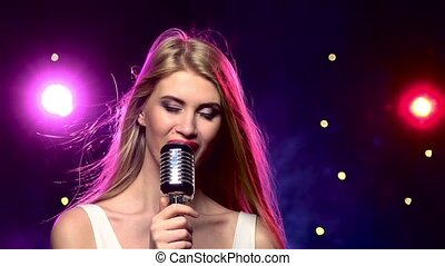 Glamour singer girl with retro microphone, her long blonde hair developing, against strobe lighting effect, close up, slow motion