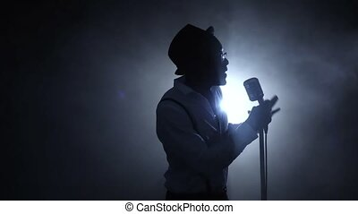 Singer half of the turnover in the smoke and white light singing at the microphone. Black background. Silhouette. Slow motion