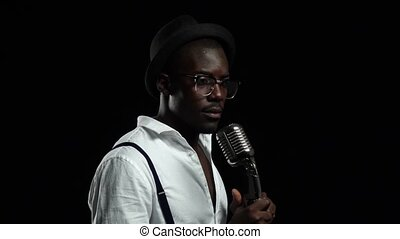 Singer holding his microphone and gesticulating hands sings. Black background. Slow motion. Close up