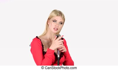 Singer in a red dress is singing into a retro microphone....