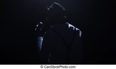 Singer in the dark with a weak light at the microphone singing the song. Black background. Silhouette. Slow motion. Close up