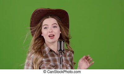 Singer in the image of a cowboy sings in a retro microphone....